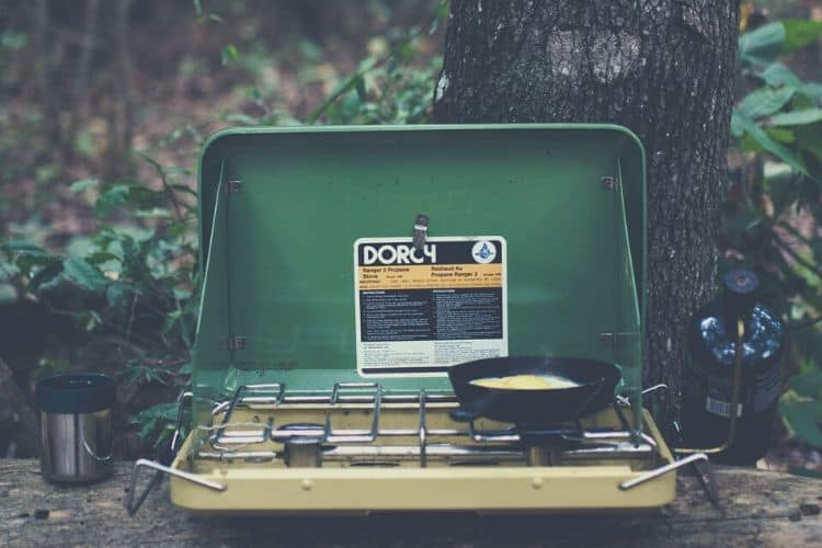camping stove with cooked egg on pan